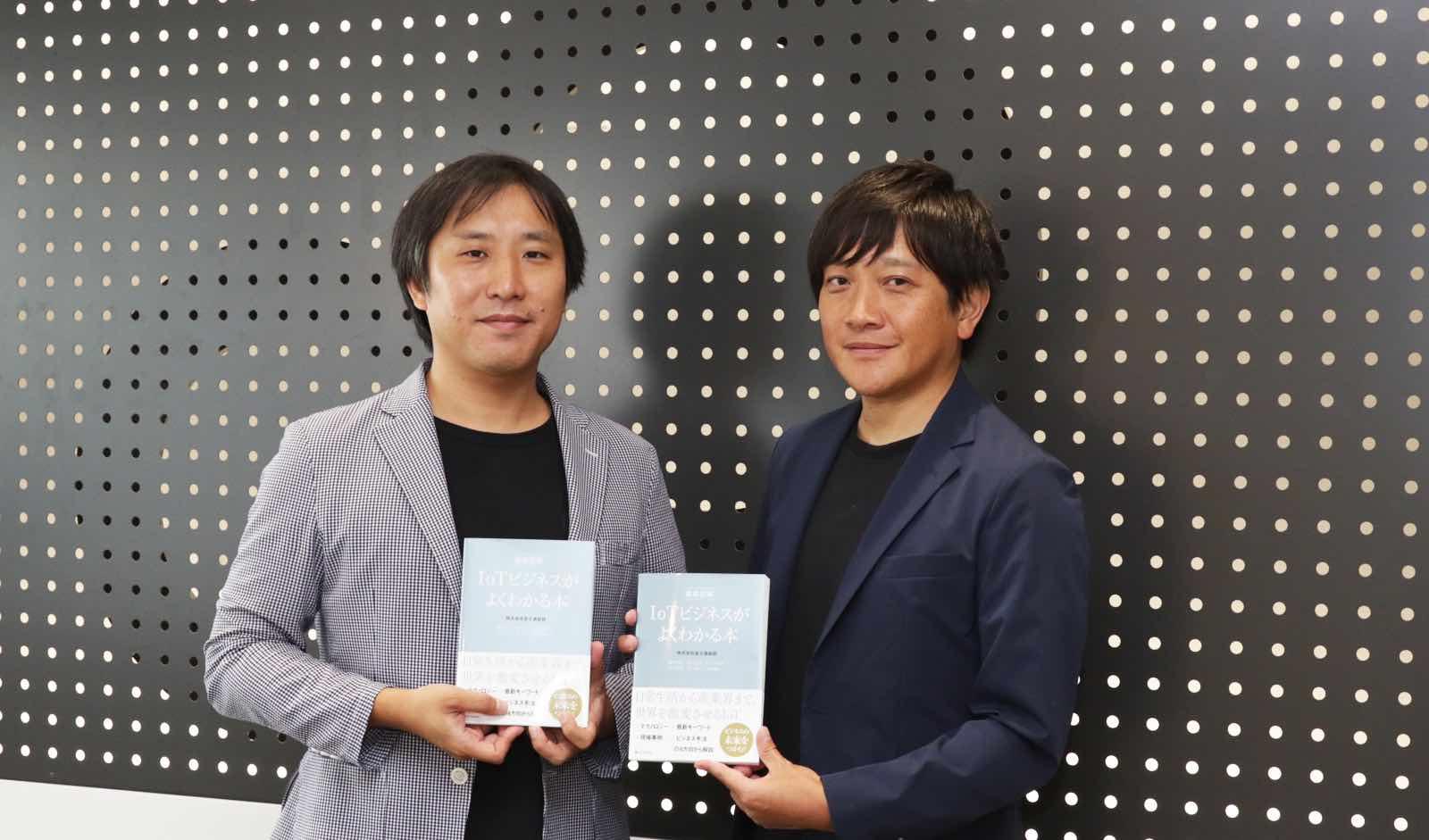 書籍「徹底図解 IoTビジネスがよくわかる本」を手にする富士通総研 佐々木 哲也氏(左)、菊本 徹氏(右)