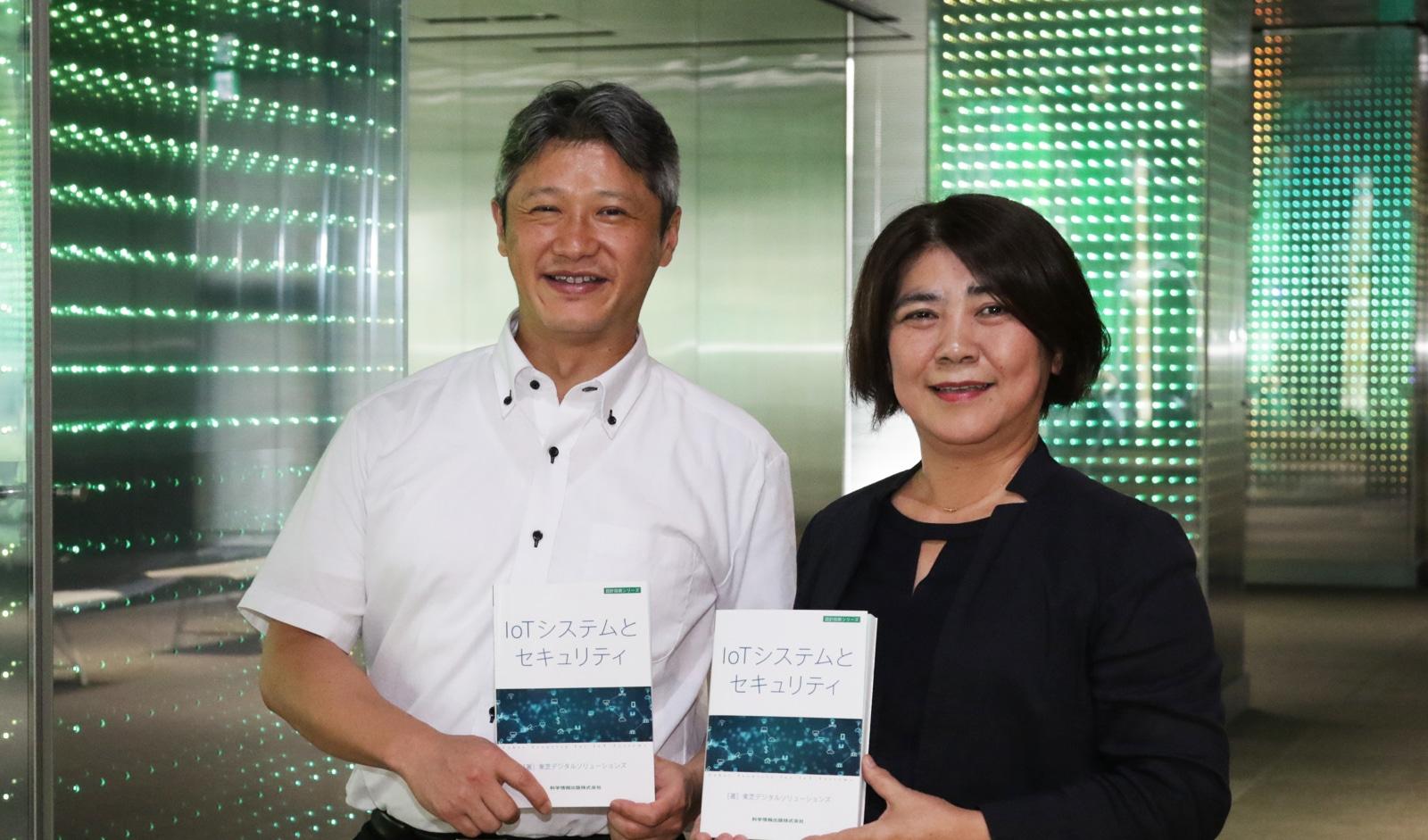 書籍「IoTシステムとセキュリティ」(科学情報出版)を手に持つ、株式会社 東芝 岡田 光司氏(左)と斯波 万恵氏(右)